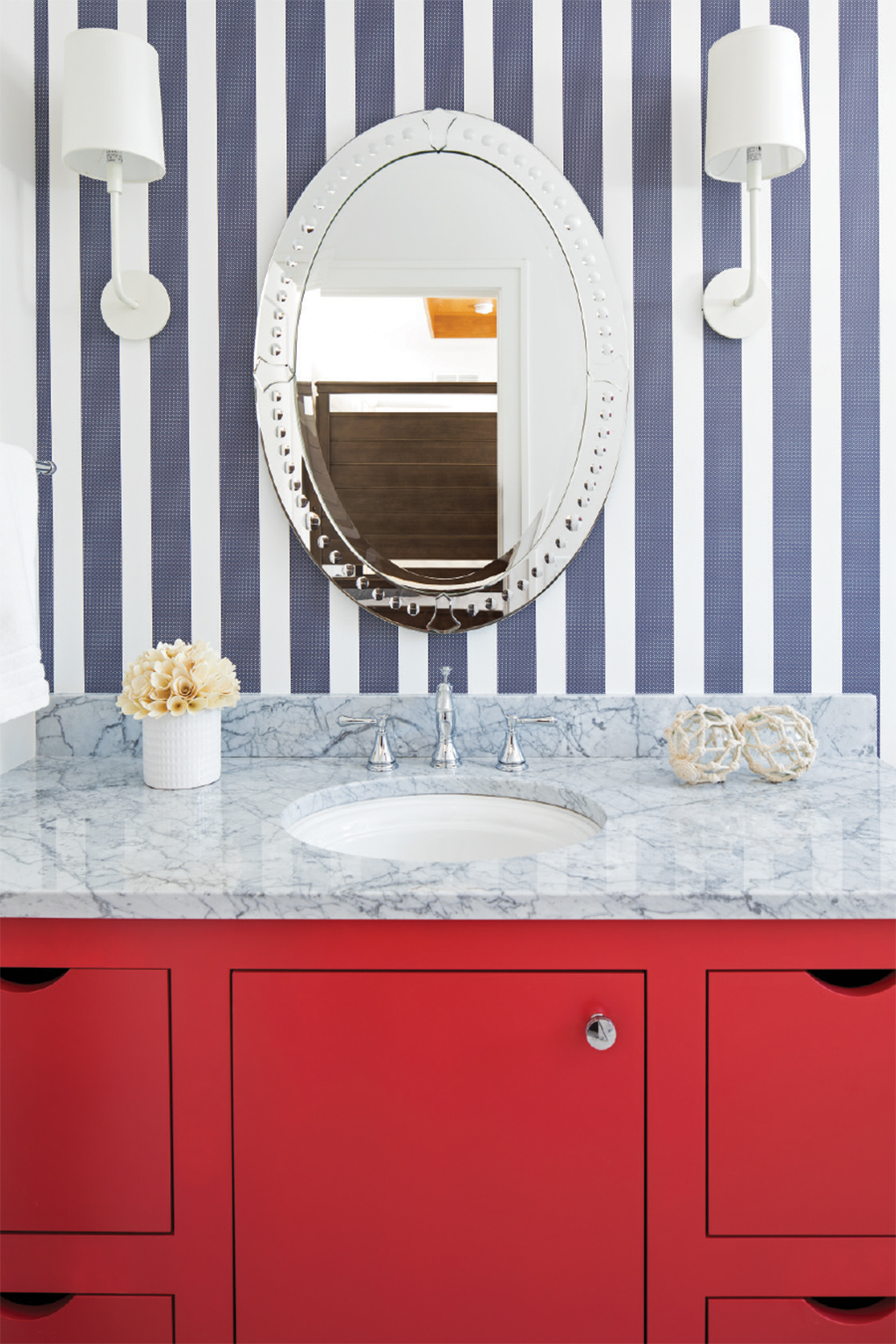A bathroom with a red vanity and blue-striped wallpaper.