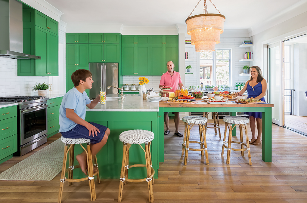 A family enjoying snacks in their kitchen with green cabinetry and, stainless steel appliances and white subway tile.