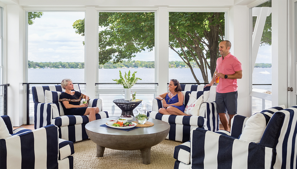 Three people relaxing in a screen porch on a lake.