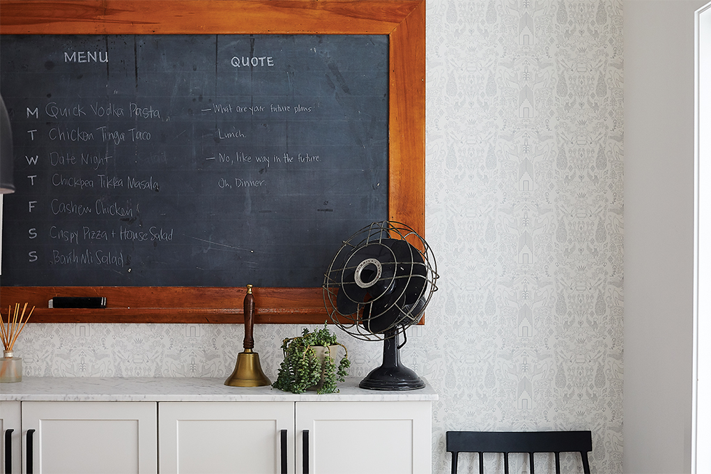 Vintage and functional: An antique fan, dinner bell, and chalkboard in the dining room.