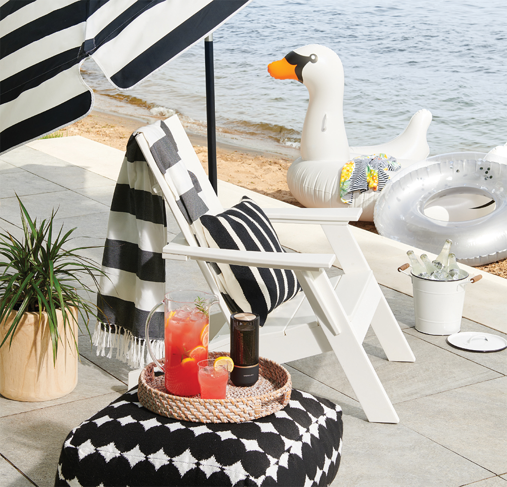 An outdoor accessory picture featuring a white deck chair with a tray of beverages and umbrella next to water.