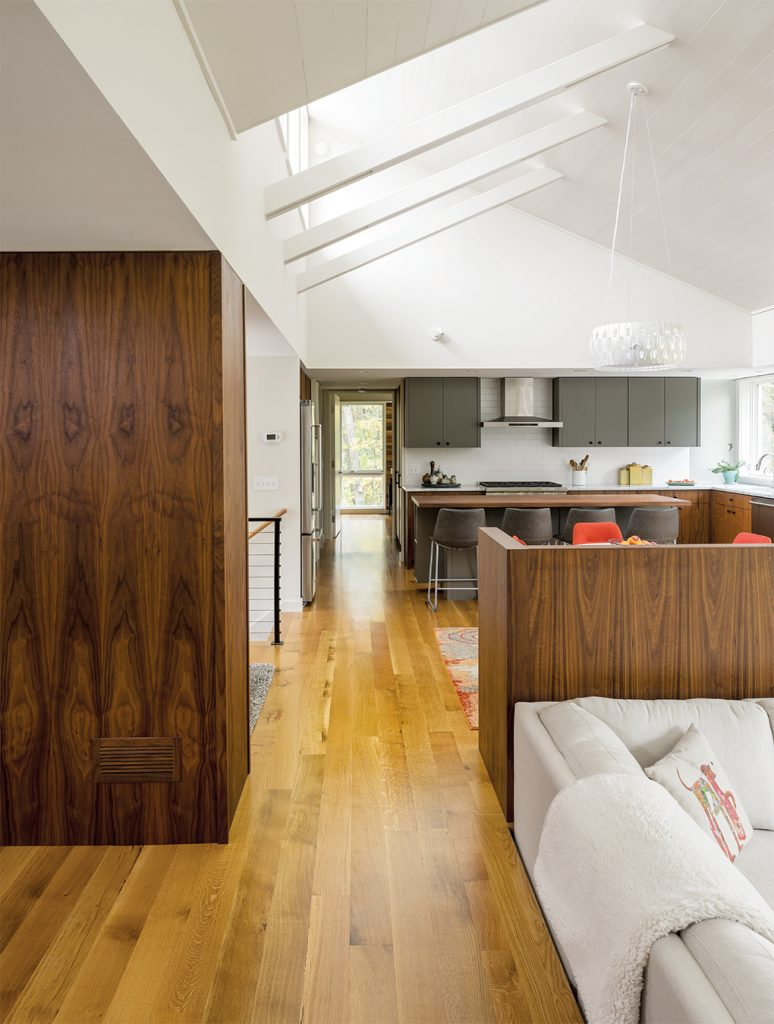 A kitchen built by SALA Architects with clerestory windows, high ceilings, and walnut cabinets.