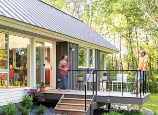 The exterior of a home built by SALA Architects features a patio with the home's owners lounging on it.