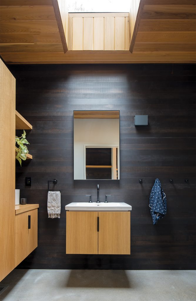 A bathroom designed by Strand Design features a wall of black-coated Douglas fir, skylight, and rift-sawn white oak floating vanity.