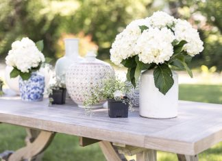 Vases with flowers on a wooden table