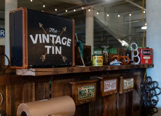 Part of Vintage Tin's store front. Wood counter, their logo, and more antique, original trinkets