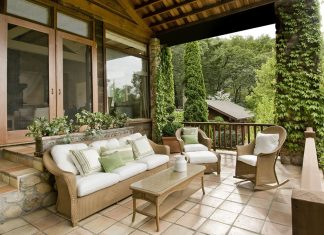 A beautiful patio with seating and plenty of greenery in the background.