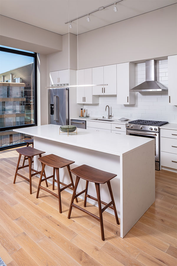 An all white kitchen with light wood flooring inside a room at 365 Nicollet, one of the stops on Midwest Home's 2018 Luxury Loft and Condo Tour.