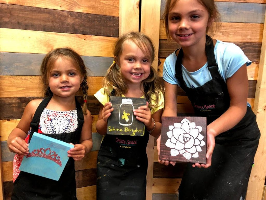 Three girls holding mini signs.