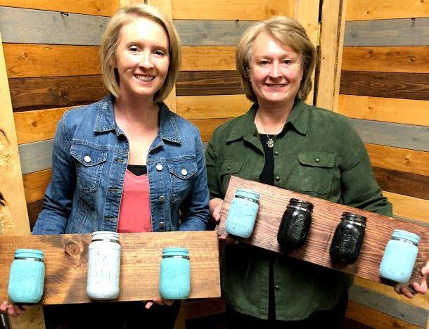 Two women holding mason jar holders.