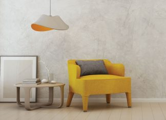 A yellow chair sits next to a table and hanging lamp at the 2018 ASID MN sample sale.