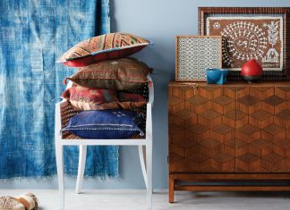 A room with decor influenced by the east features a blue rug, blue curtains, blue wall, chair, and table.