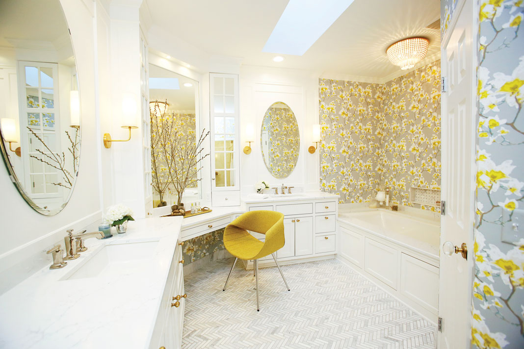 An all white bathroom with herringbone tile, a yellow chair, and yellow flower wallpaper designed by ImPeckable Design, Inc.