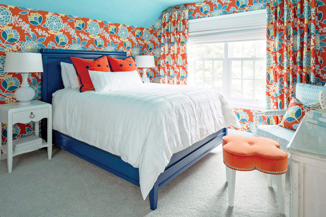 A blu bed with white bedspread and red pillows sits in a room with red and blue flower wallpaper designed by Martha O'Hara Interiors.