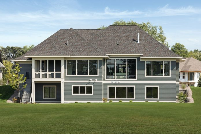 The back exterior of a large, gray home on Midwest Home's 2018 Luxury Home Tour that shows a lot of windows, and plenty of green grass.