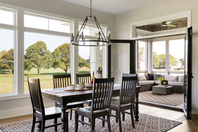 The dining room in a home featured on Midwest Home's 2018 Luxury Home Tour that features a table with seating, chandelier hanging overhead, and large windows overlooking trees.