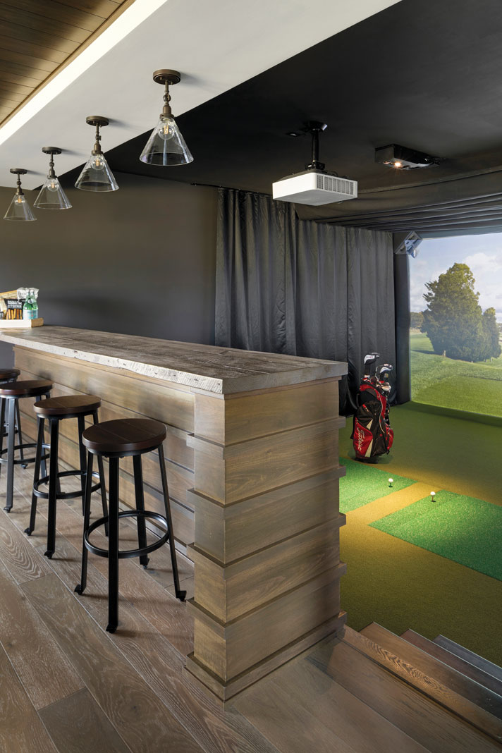 The golf simulator in the rambler's lower level is the most unique aspect of the home–it can double as a video player, and nearby bar seating allows for spectator viewing. Part of Midwest Home's 2018 Luxury Home Tour.