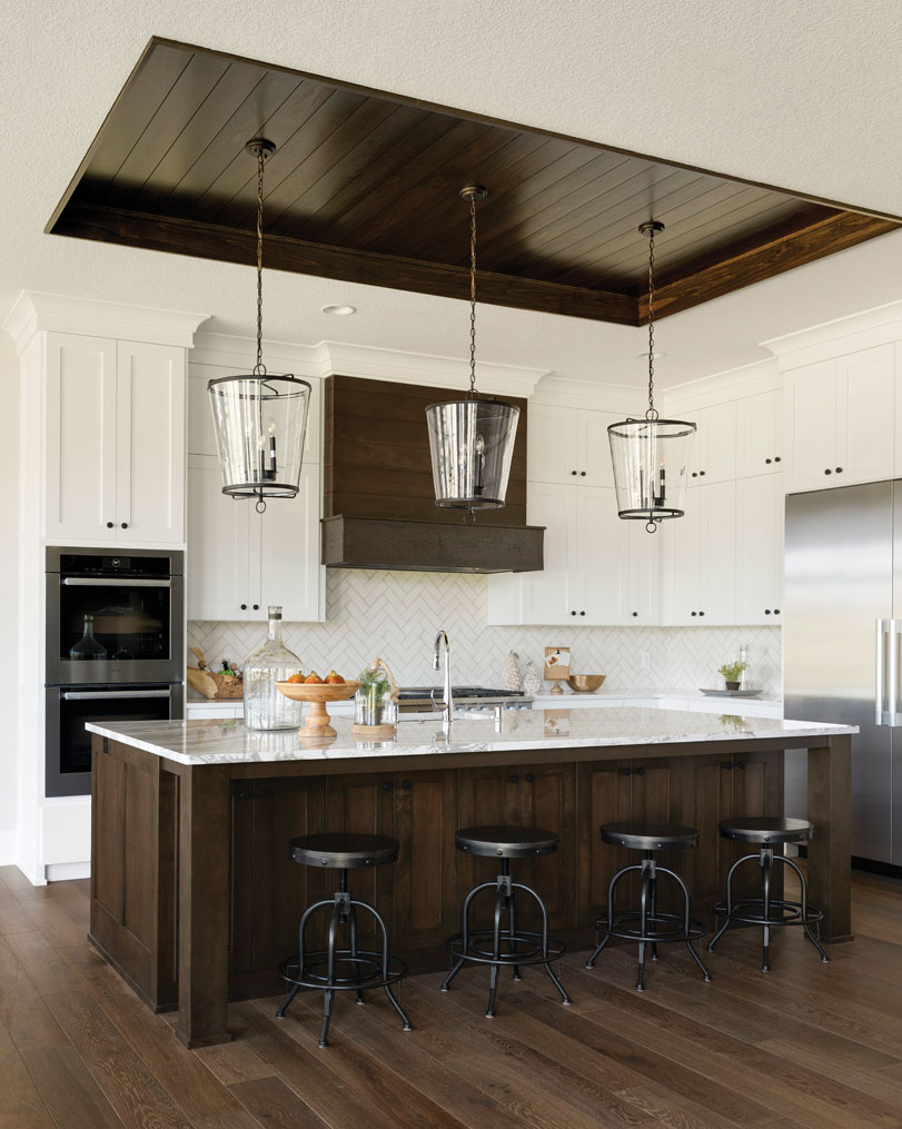 The kitchen features custom cabinetry, Cambria countertops, and dark-stained millwork inset above the island. Part of Midwest Home's 2018 Luxury Home Tour.