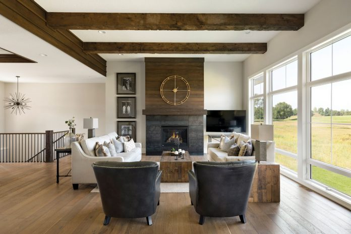 A living room in a home on Midwest Home's 2018 Luxury Home Tour that shows plenty of seating surrounding a table next to a fireplace with a large clock above it. Large windows overlooking trees are situated on the right.