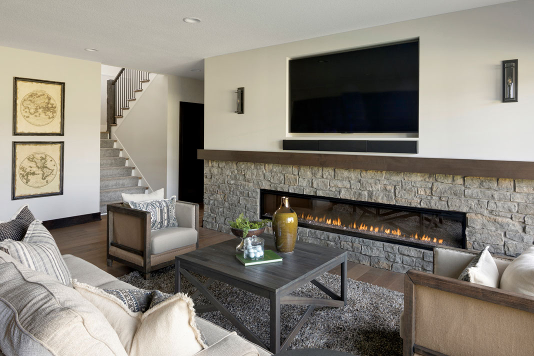 The lower level offers a stone-clad electric fireplace perfect for cozying up to during the colder months. Part of Midwest Home's 2018 Luxury Home Tour.