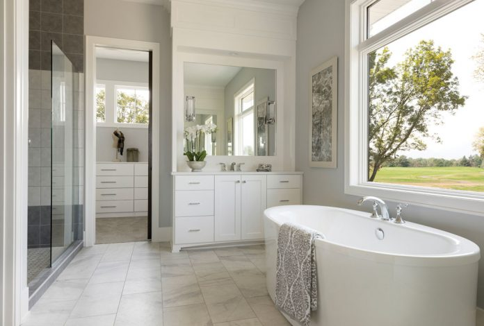 A bathroom in a home on Midwest Home's 2018 Luxury Home Tour that features an all white soaking tub, white vanity, and large window overlooking some trees.