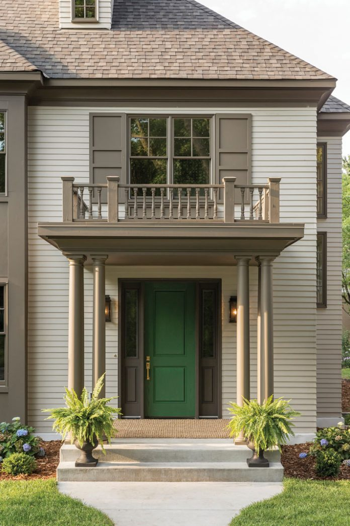 The entry of a home on Midwest Home's 2018 Luxury Home Tour that features a small deck overhanging a green door.