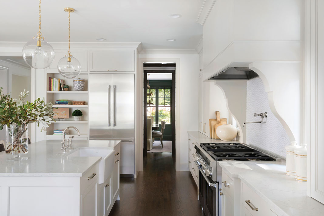 In the kitchen, modern light fixtures hang over the marble-like island, which includes a large farmhouse sink. Part of Midwest Home's 2018 Luxury Home Tour.