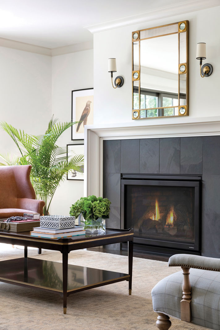 A sleek black stone fireplace acts as the focal point of the home's great room, while an overhead mirror, flanked by twin sconces, accentuates its simple elegance. Part of Midwest Home's Luxury Home Tour 2018.