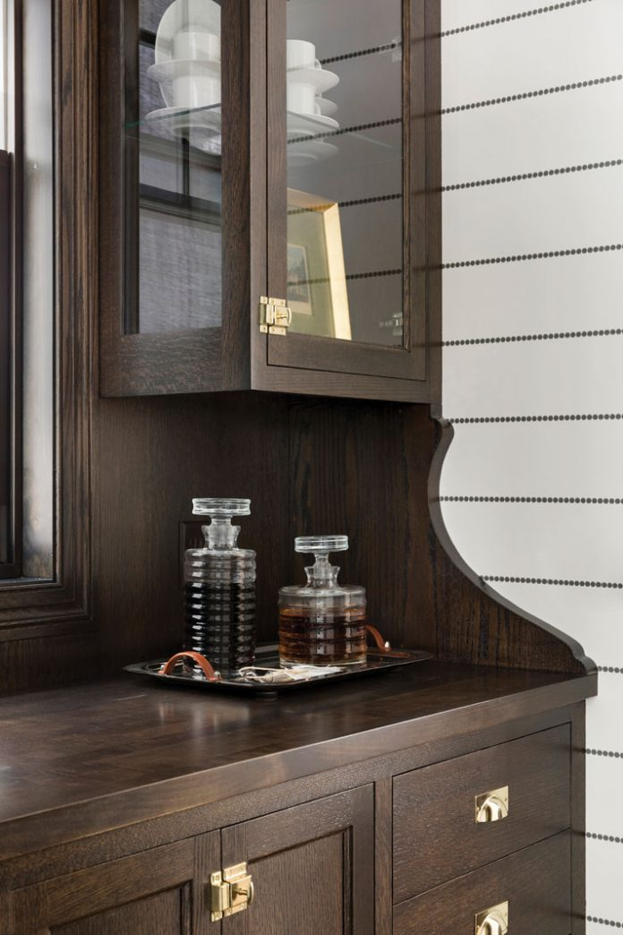 A pantry in a home on Midwest Home's 2018 Luxury Home Tour that shows alcohol sitting on a dark wood cabinet.