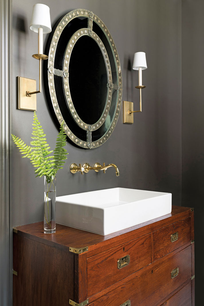 An antique, English campaign chest used as the vanity in the main-level bathroom. Part of Midwest Home's 2018 Luxury Home Tour.