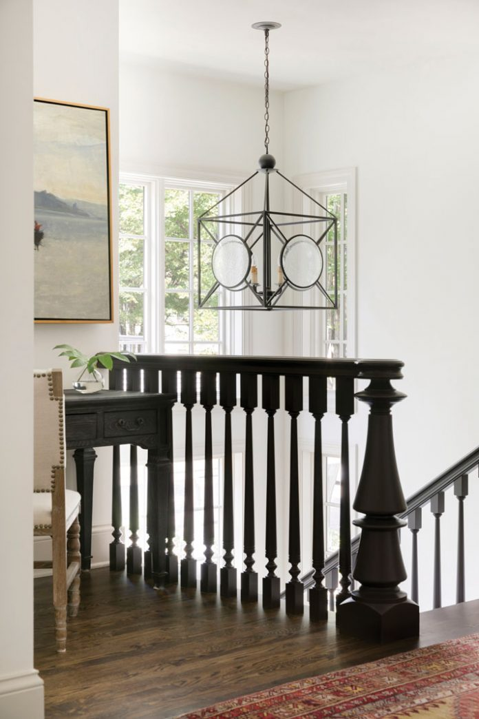 The top of a stairwell in a home on Midwest Home's 2018 Luxury Home Tour that shows a dark wood railing, and chandelier hanging over it.