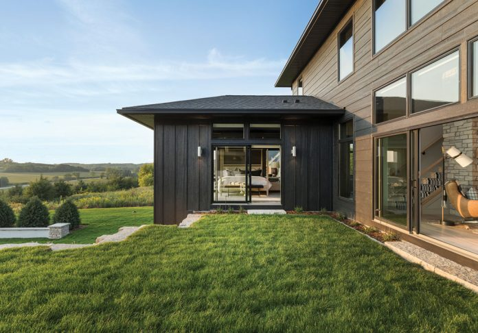 The exterior of a home on Midwest Home's 2018 Luxury Home Tour that shows a walkway out onto some grass on the backside of the home.