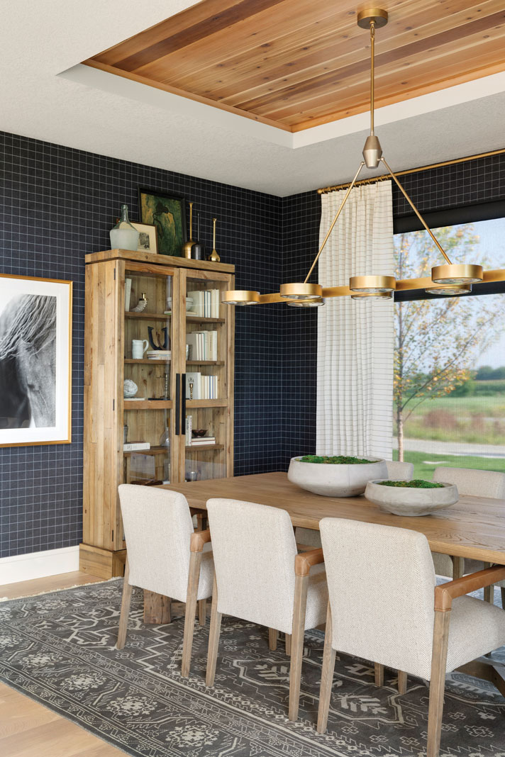 The formal dining room exemplifies the home's unique combination of materials and textures with navy plaid wall coverings and cedar strips inset into the ceiling. Part of Midwest Home's 2018 Luxury Home Tour.