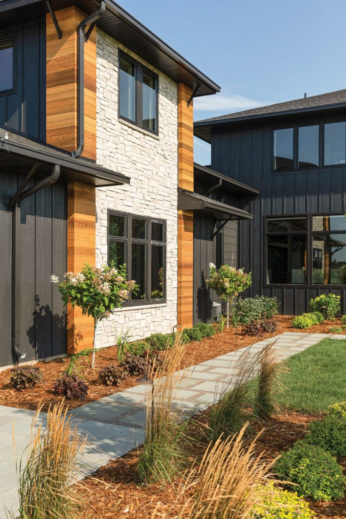 The exterior of a home on Midwest Home's 2018 Luxury Home Tour that features green landscaping with mulch in front of a two-story home with wood and stone accents.