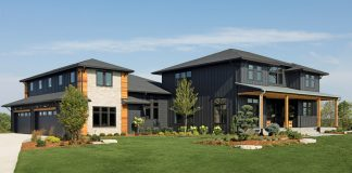 Designed by Divine Custom Homes, this new home's contemporary, mountain-lodge style is heightened by black board-and-batten siding and stone, cedar, and iron accents.