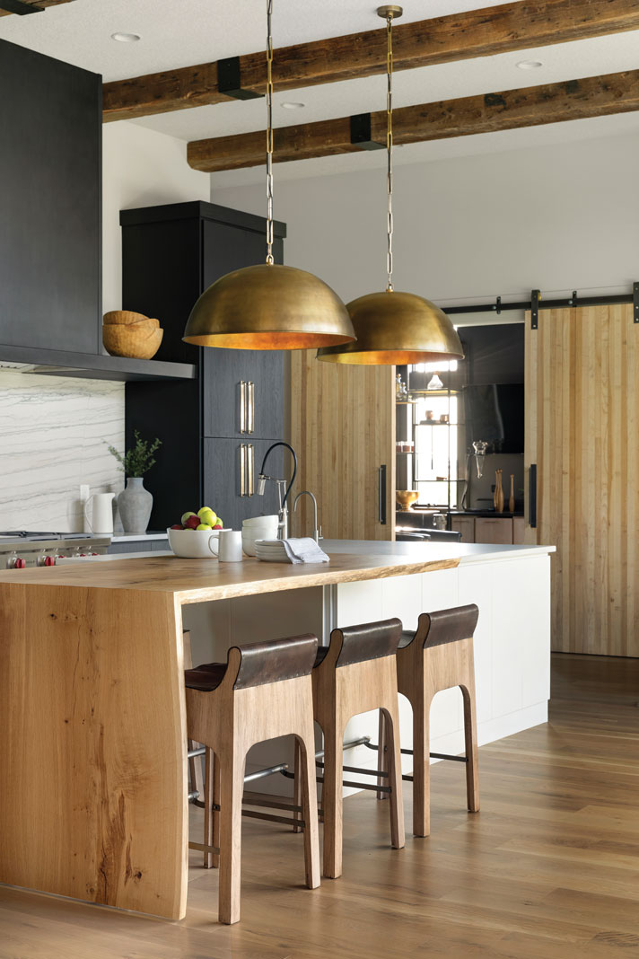 Twelve-foot-high ceilings and giant brass pendants hanging over the island make the kitchen stand out, while painted oak cabinets and whitewashed oak plank flooring lend a chic farmhouse feel. Part of Midwest Home's 2018 Luxury Home Tour.