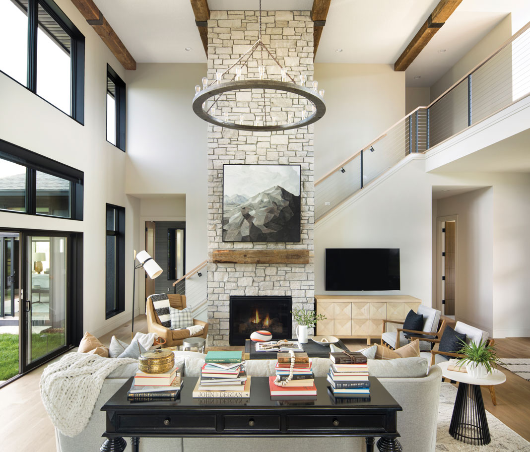 In the great room, a two-story stone fireplace serves as the hub of the home, while a circular chandelier casts a warm glow over the area. Part of Midwest Home's 2018 Luxury Home Tour.