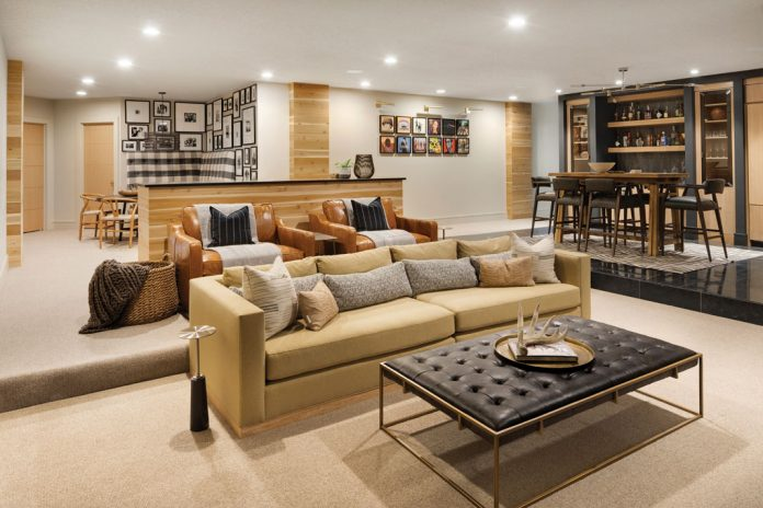 The lower level of a home on Midwest Home's 2018 Luxury Home Tour that features multiple areas for seating and wood panel accents.