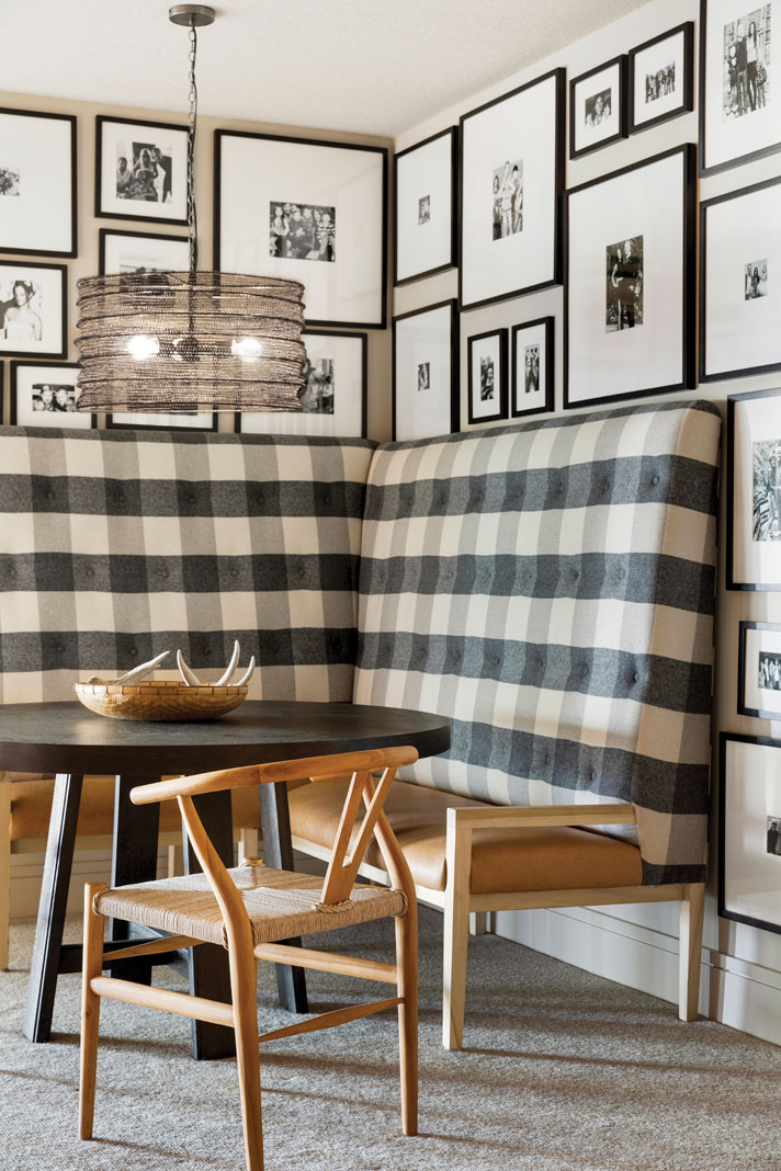 In the lower level, a plaid banquette surrounded by black-and-white framed photos is a cozy place to gather. Part of Midwest Home's 2018 Luxury Home Tour.