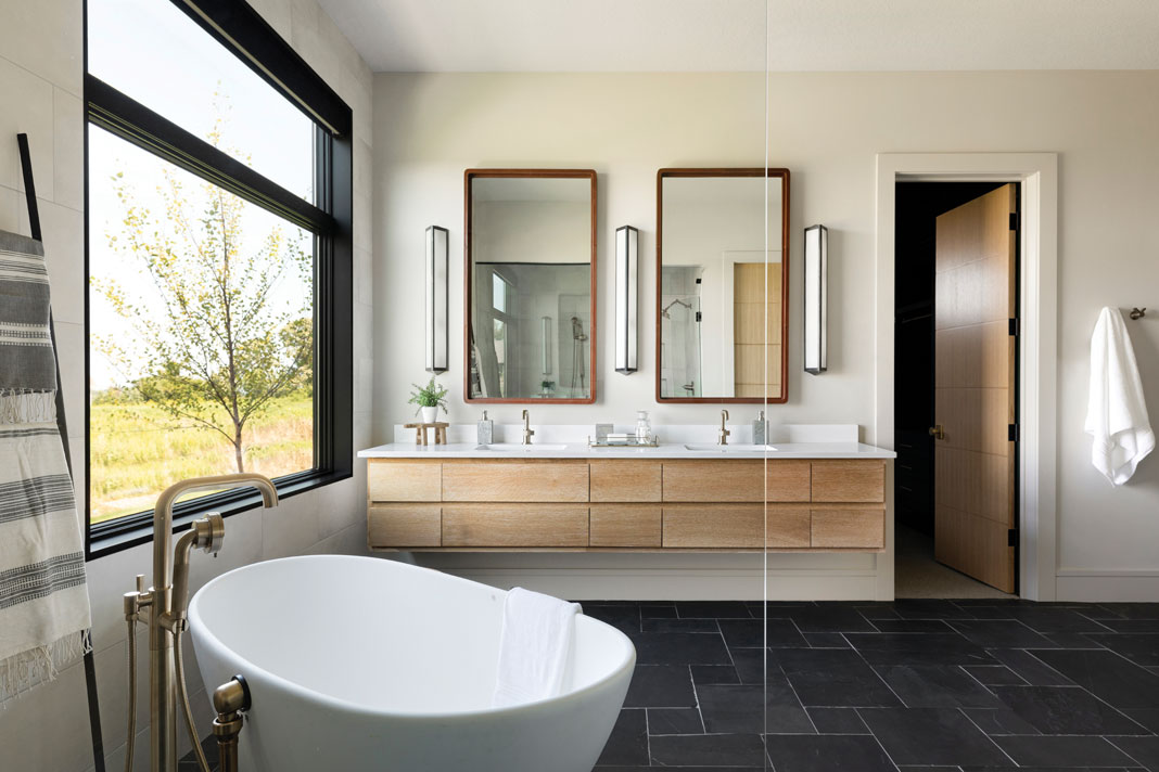 The master bath offers custom leather-wrapped mirrors mounted over twin sinks, as well as a large soaking tub perfect for relaxing. Part of Midwest Home's 2018 Luxury Home Tour.