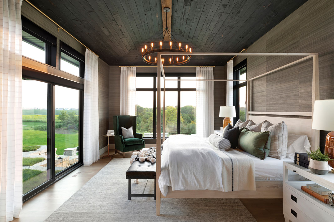 The master bedroom features grasscloth wallpaper and a circular chandelier echoing the one in the great room. Part of Midwest Home's 2018 Luxury Home Tour.