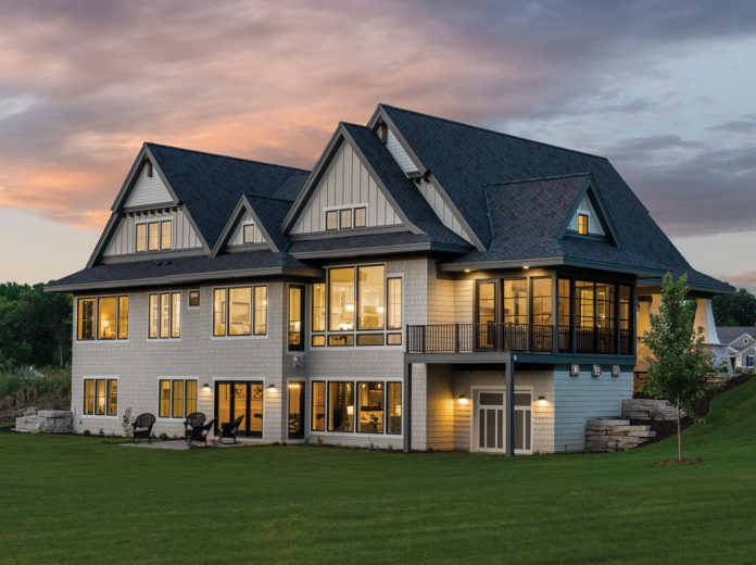 The exterior of a large home on Midwest Home's 2018 Luxury Home Tour that shows a plethora of windows with light illuminating from them at dusk.