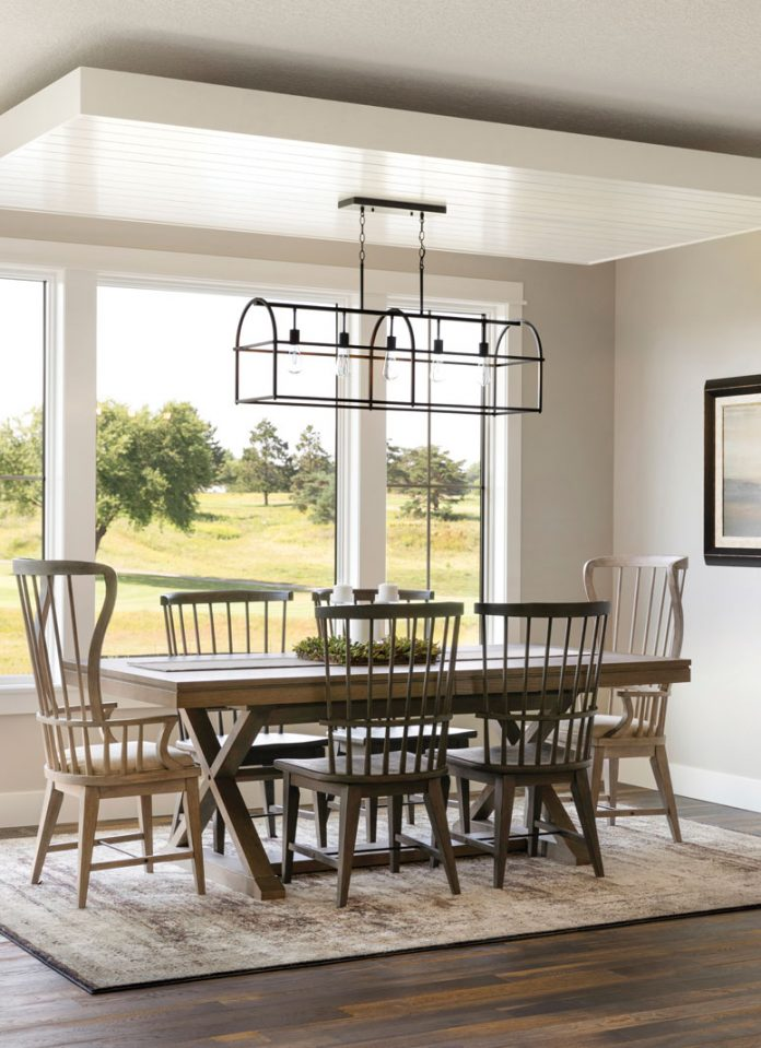 The dining room in a home on Midwest Home's 2018 Luxury Home Tour that shows a small table with surrounding chairs underneath a chandelier that overlooks an abundance of trees.