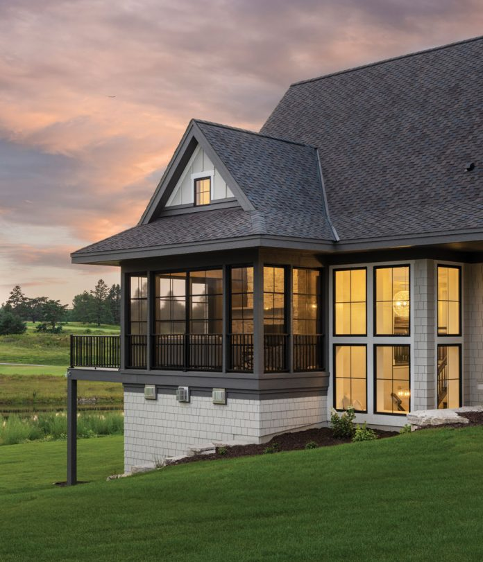 The exterior of a home at duck on Midwest Home's 2018 Luxury Home Tour that shows windows with light illuminating a second-level patio.