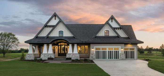 The front exterior of a home on Midwest Home's 2018 Luxury Home Tour that shows steepled features, pillars, and driveway.