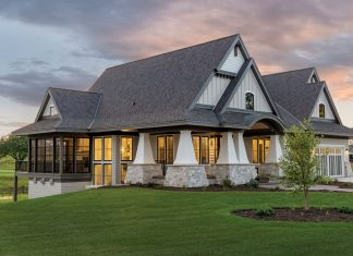 Stately tapered columns with wide stone foundations are a striking element in the exterior of this new modern cottage by Hartman Homes. Part of Midwest Home's 2018 Luxury Home Tour.