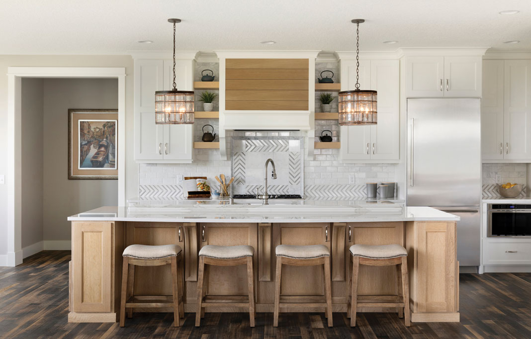 Quartz countertops and a marble backsplash offset the kitchen's cerused oak cabinetry and white oak flooring. Part of Midwest Home's 2018 Luxury Home Tour.