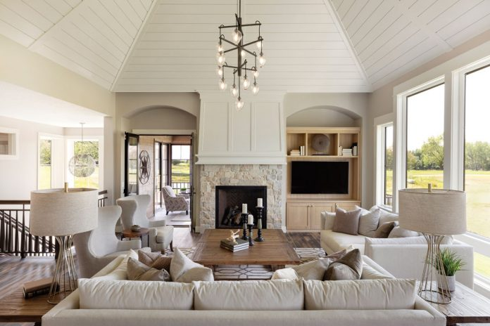 The living room of a home on Midwest Home's 2018 Luxury Home Tour that features an abundance of seating surrounding a table, all next to a fireplace and adjacent television with a chandelier hanging overhead.