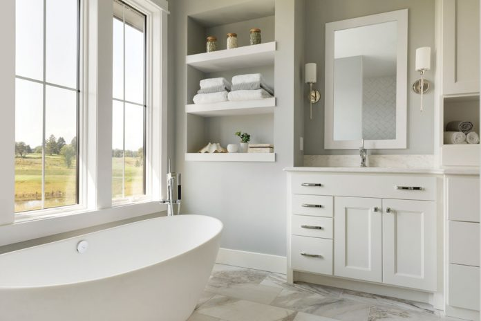 A bathroom in a home on Midwest Home's 2018 Luxury Home Tour that features a white soaking tub, white cabinetry stocked with towels, and a large mirror.