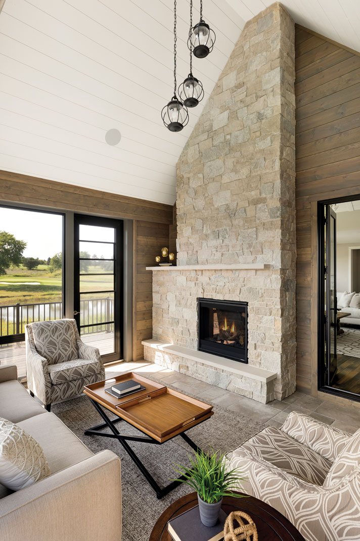 A three-season porch located off the home's great room features the same vaulted ceiling in white shiplap detail and beautiful stone accents found in the main living area. Part of Midwest Home's 2018 Luxury Home Tour.